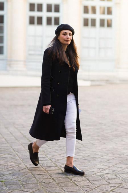 Девушка в белых джинсах, черном пальто и берете