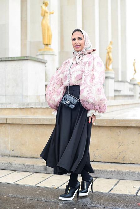Девушка в черной длинной юбке, розовая блуза с принтом, маленькая сумочка
