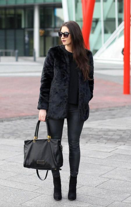 Девушка в черной шубе и черных узких брюках