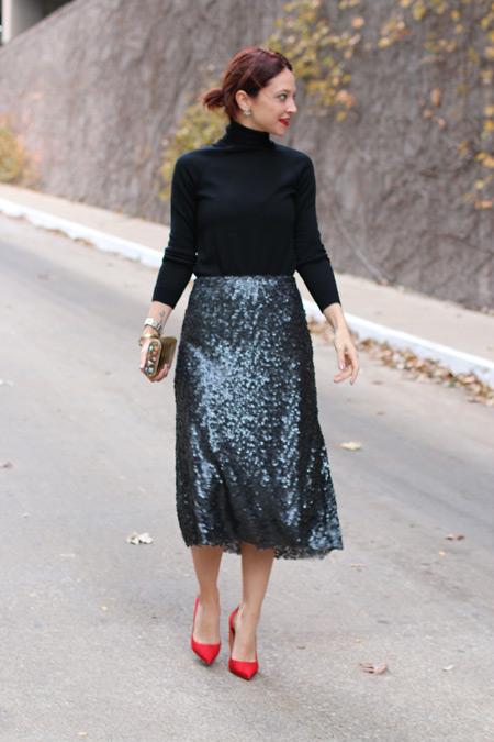 Девушка в черной водолазке и блестящей юбке