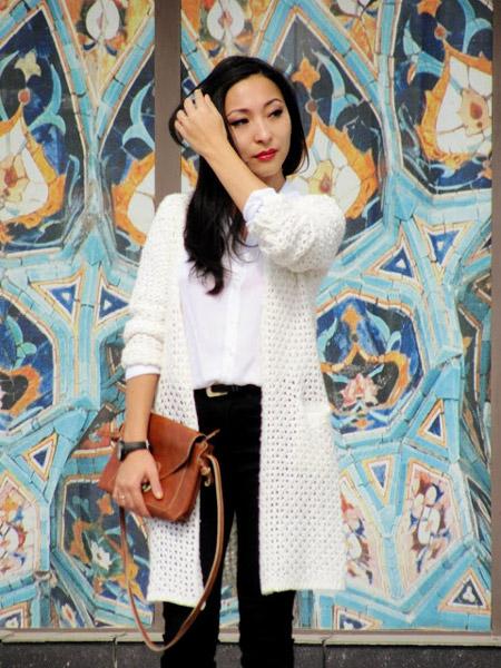 Девушка в черных брюках и белом кардигане