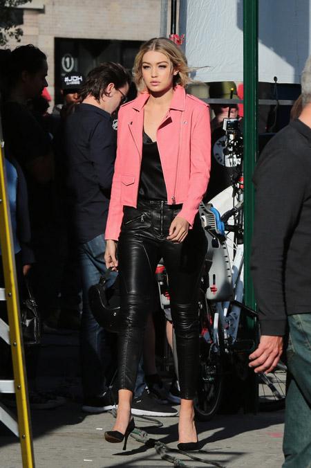 Девушка в черных туфлях, кожанных брюках, черный топ и розовый жакет