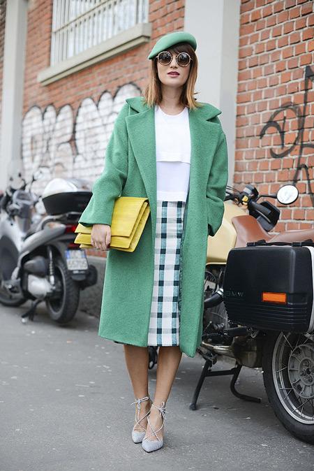 Девушка в клетчатой юбке, зеленом пальто и берете