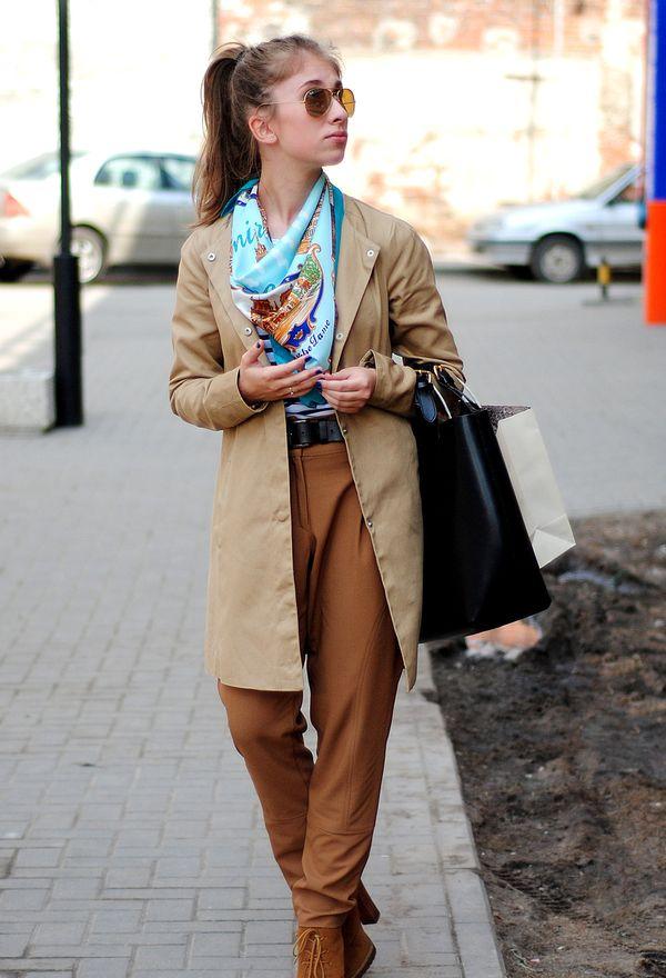 Девушка в коричневых брюках и бежевом плаще