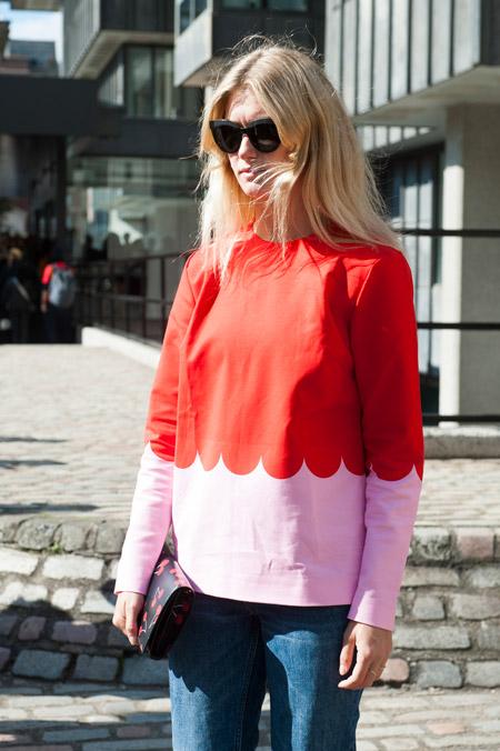 Девушка в красно розовом свиншоте и синих джинсах