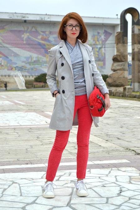 Девушка в красных брюках и сером плаще