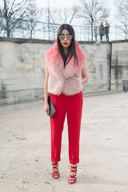 Девушка в красных брюках со стрелками, босоножках и розовом меховом жилете