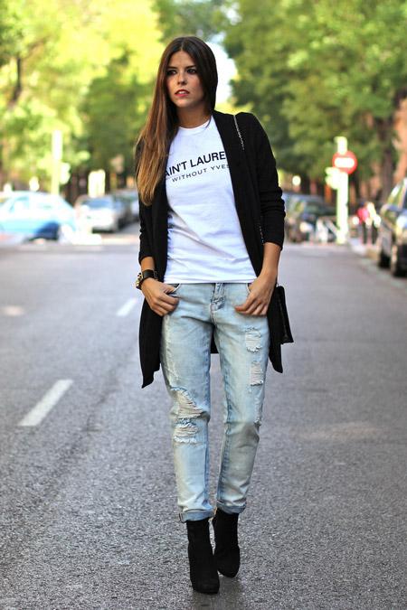 Девушка в потертых джинсах и черном кардигане