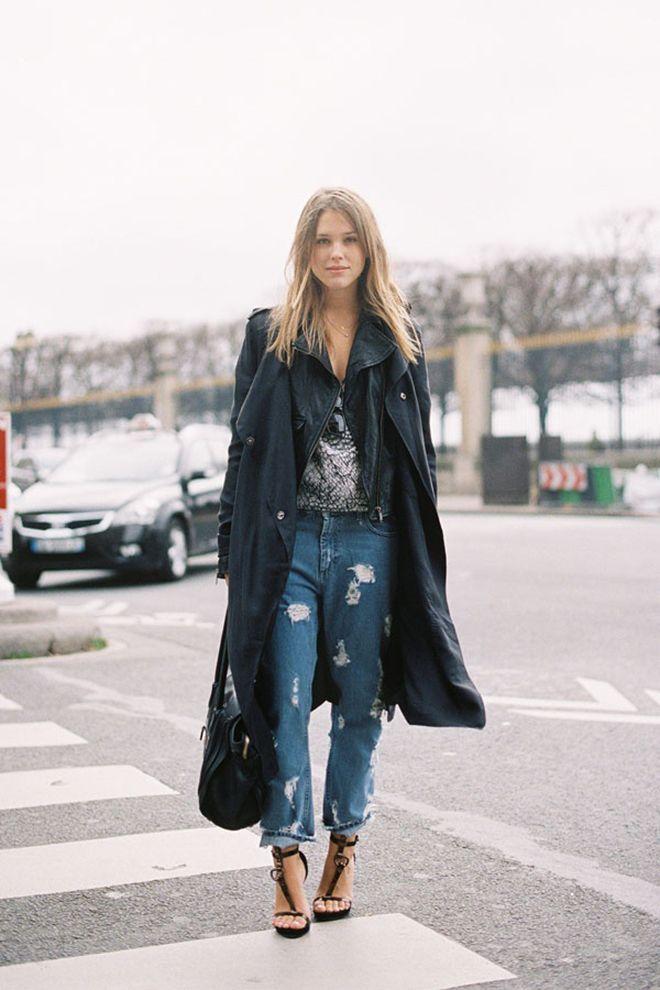 Девушка в потертых джинсах и черном плаще