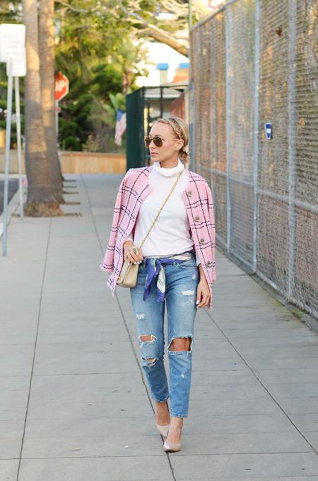Девушка в рваных джинсах и белой водолазке
