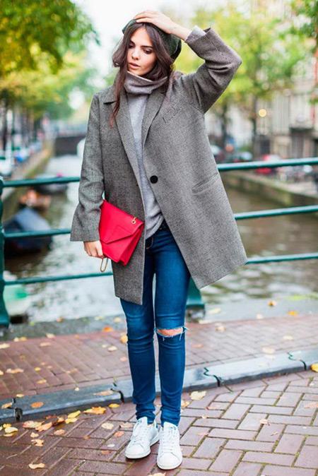 Девушка в рваных джинсах и серой водолазке