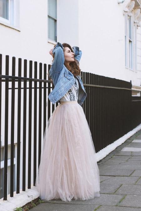 Модель в длинной светло розовой юбке макси, футболке и джинсовке