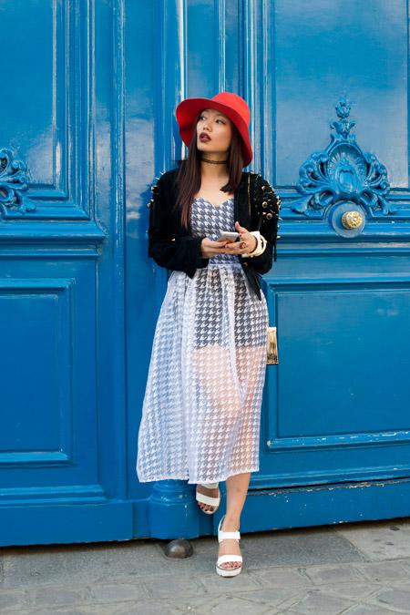 Модель в платье с белым прозрачным подолом, сандалии, черная куртка и красная шляпа