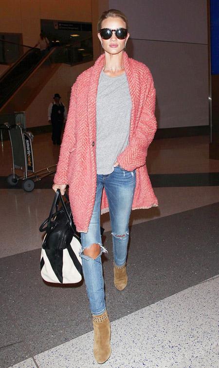 Модель в розовом драповом пальто, синих джинсах, серая футболка и коричневые ботильоны