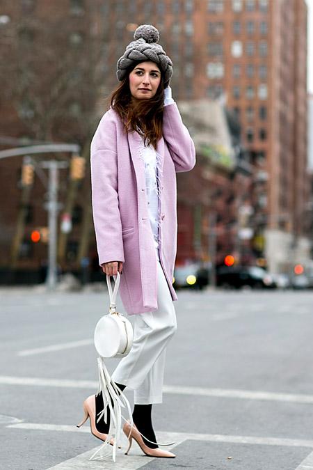 Модель в розовом пальто прямого кроя, белых брюках капри и мехой шапке с помпоном