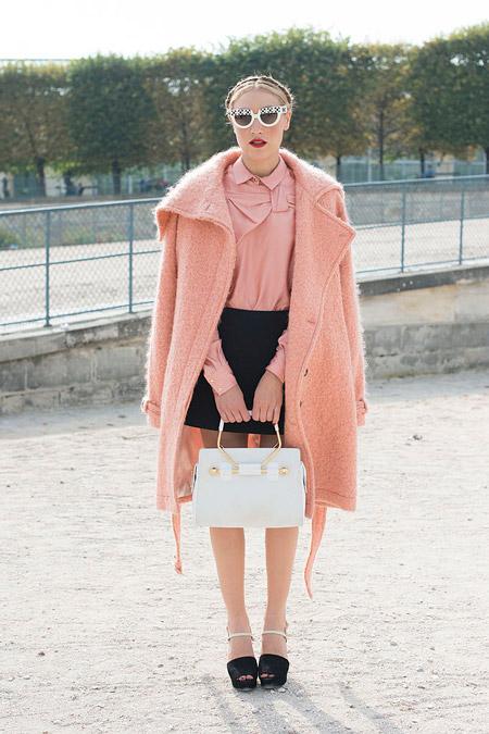 Модель в розовом пальто, розовая блуза с бантом и черная мини юбка