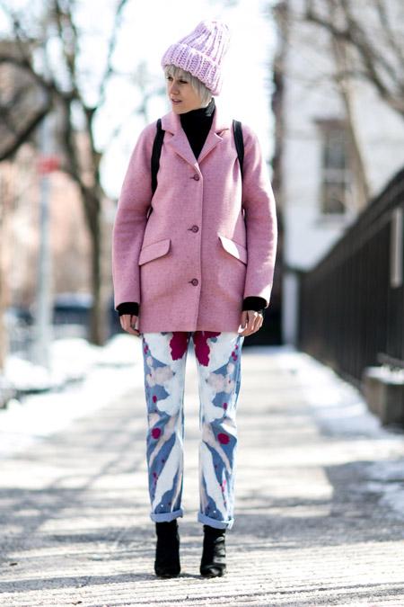 Модель в розовом пальто, розовая вязанная шапка, разноцветные брюки и черная водолазка