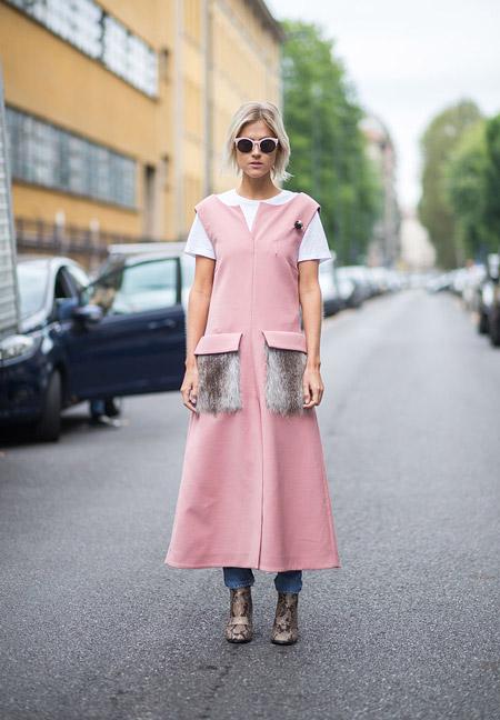 Модель в розовом плаще без рукавов с накладными меховыми карманами, белая футболка и голубые джинсы