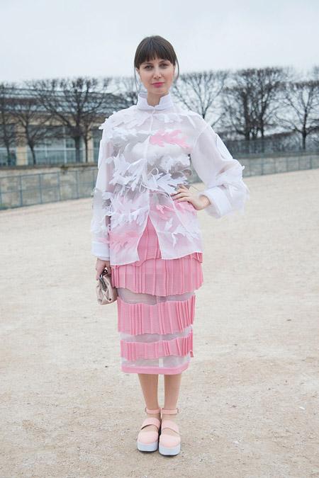 Модель в розовом платье с прямой юбкой, белая полупрозрачная блуза и слипоны на высокой подошве