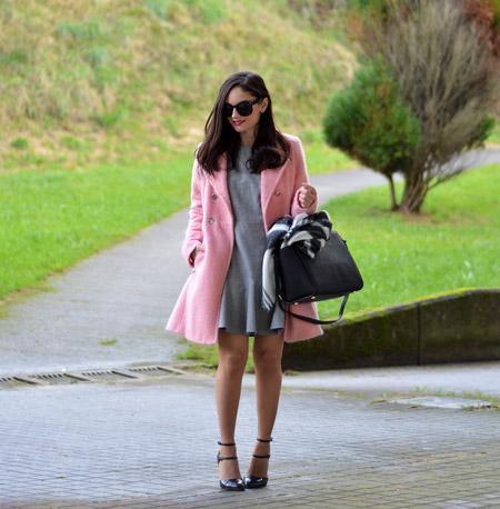 Модель в розовом приталенном пальто, серое платье, черная большая сумка и туфли
