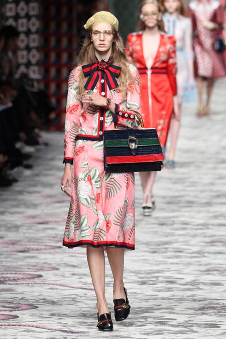 Модель в розовом юбочном костюме и золотистом браслете, показ Gucci