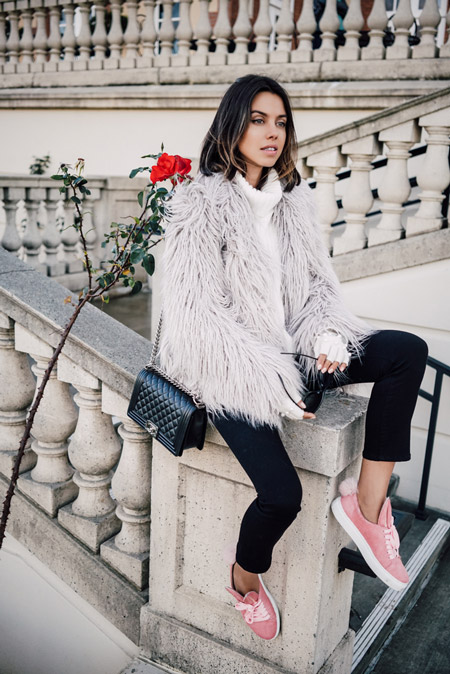 Модель в розовых кедах, меховая шуба, белый вязанный свитер и черные капри