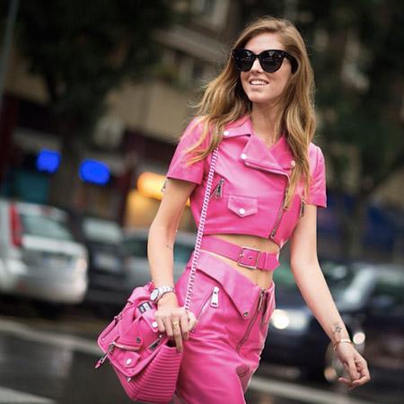 Модель в ярко розовом кожанном костюме с юбкой и розовая сумочка
