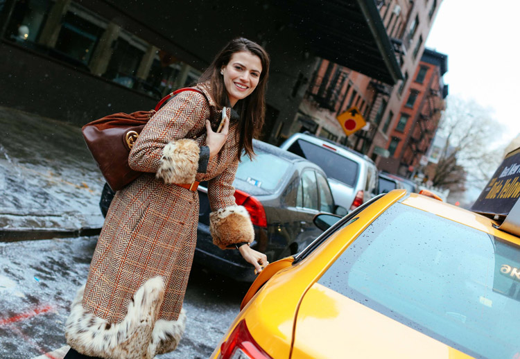 Alessandra Codinha в красивом пальто с меховыми манжетами и подолом, коричневая сумка