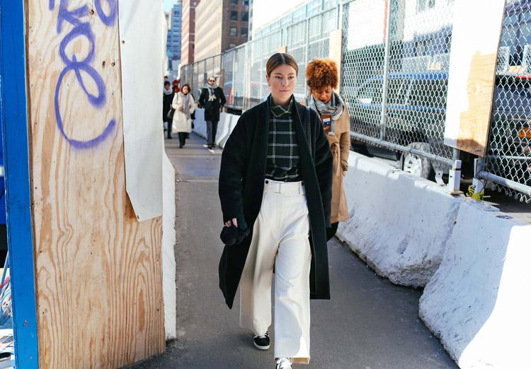 Annina Mislin в белых широких брюках, черной рубашке в клетку и черное пальто
