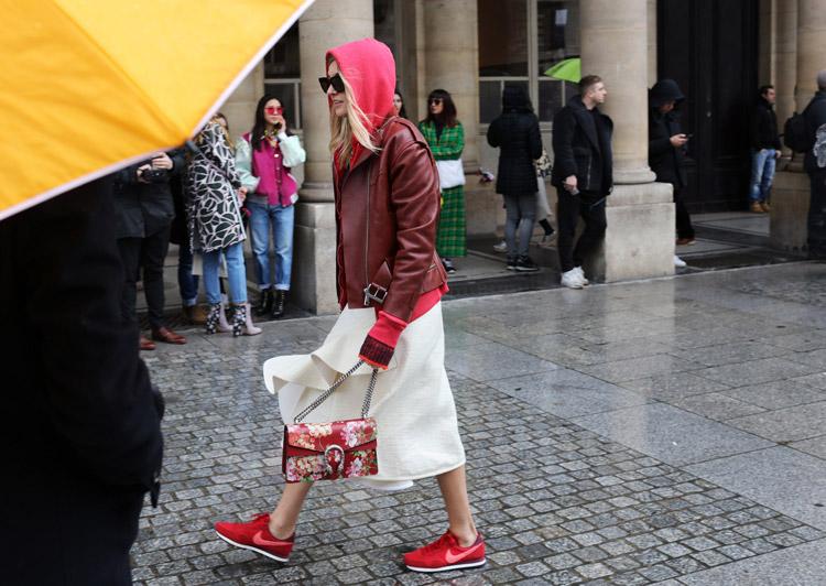 Camille Charriere в белой юбке миди, красных сникерсах, кожаная куртка и бордовая сумочка с цветами