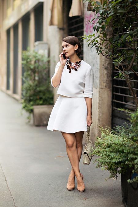 Девушка в белом косюме с юбкой, бежевые туфли и сумочка