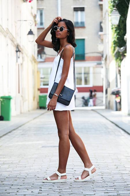 Девушка в белом мини сарафане, черная сумочка и сандалии
