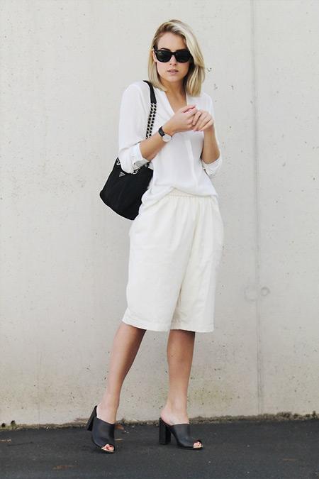 Девушка в белых бермудах, блузе и черные босоножки и сумочка