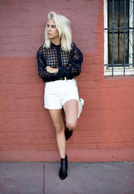 Девушка в белых шортах, темной рубашке и ботильоны