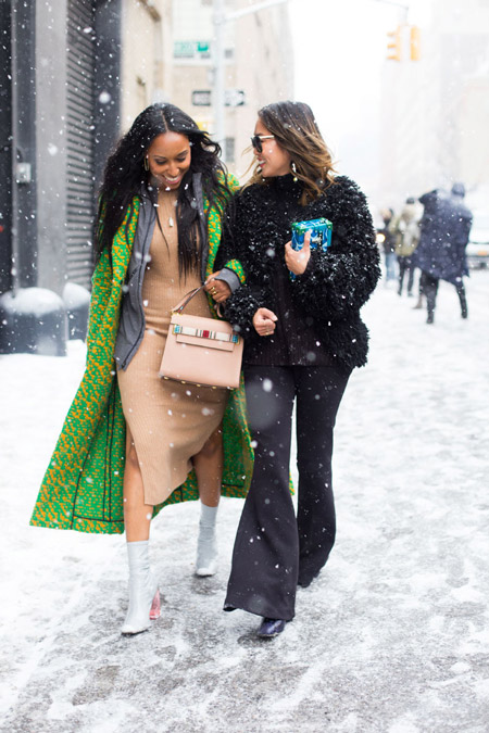 Девушка в бежевом платье с разрезами по бокам и зеленом пальто, девушка в брюках клеш и черной шубке