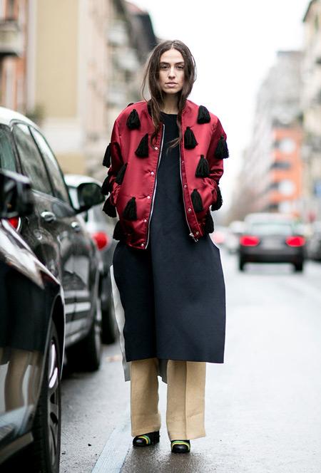 Девушка в брюках песочного цвета, черном платье и бордовой куртке с кисточками