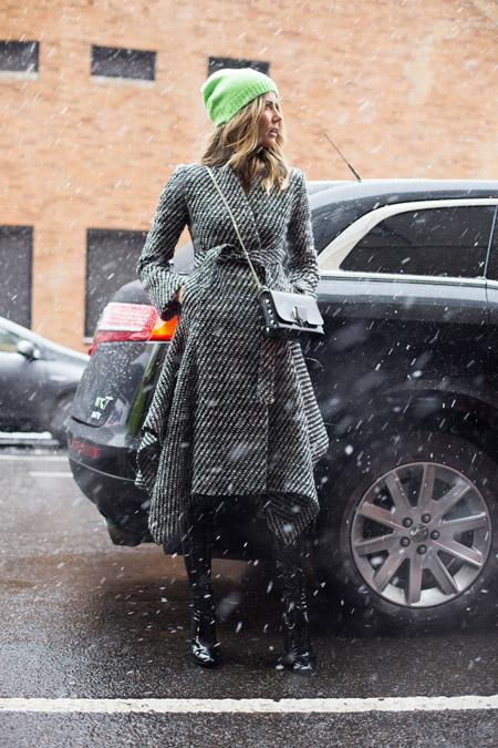 Девушка в черно-белом пальто в диагональную полоску, маленькая сумочка и зеленая шапка