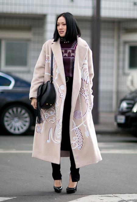 Девушка в черных брюках, кофта и светлое пальто с белым принтом, черные туфли и сумка