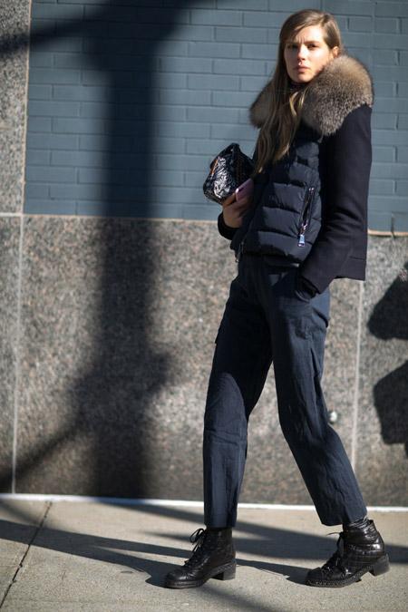 Девушка в черных брюках, пуховик с меховым воротником и черные ботинки