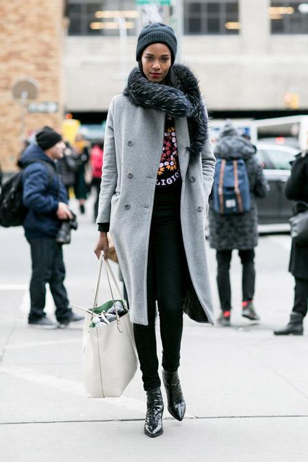 Девушка в черных джинсах, футболка с принтом. серое пальто, шапка и белая объемная сумка