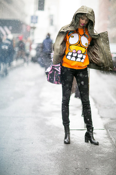 Девушка в черных джинсах, оранжевый свиншот с принтом и куртка с капюшоном