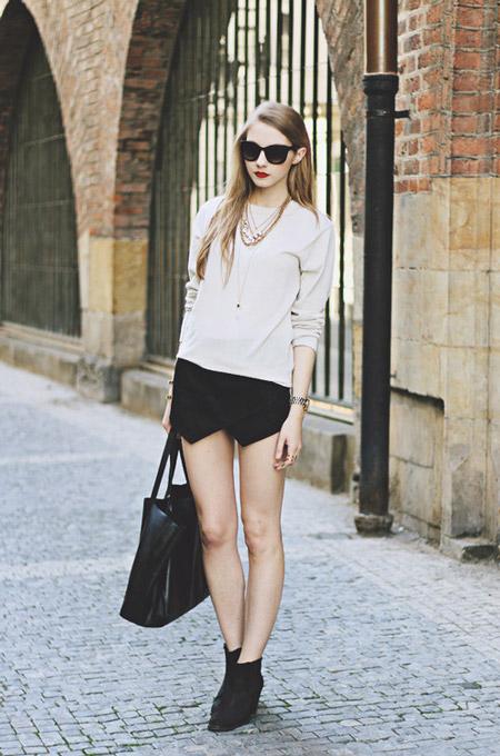 Девушка в черных шортах, бежевая кофта, сумка и ботильоны