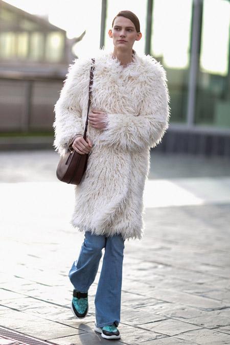 Девушка в джинсах и белой меховой шубе
