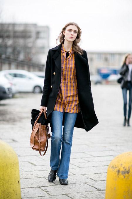 Девушка в джинсах, клетчатой рубашке и черное пальто