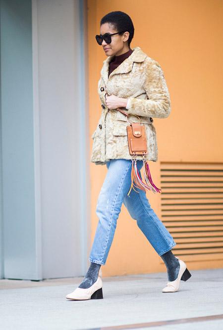 Девушка в голубых джинсах и бежевой меховой куртке
