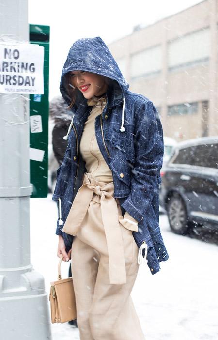 Девушка в комбинезоне молочного цвета и джинсовой куртке с капюшоном