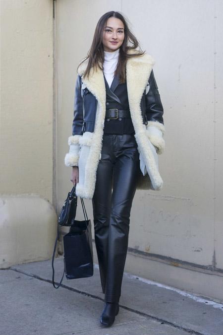 Девушка в кожаных брюках, черный кардиган и дубленка с белым мехом