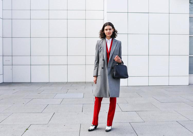 Девушка в красном брючном костюме, серое пальто и черная сумка