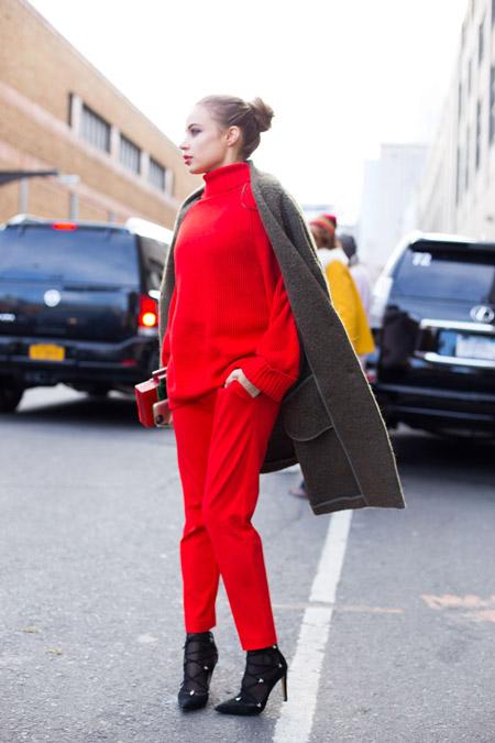 Девушка в красных брюках, свитере и коричневое пальто