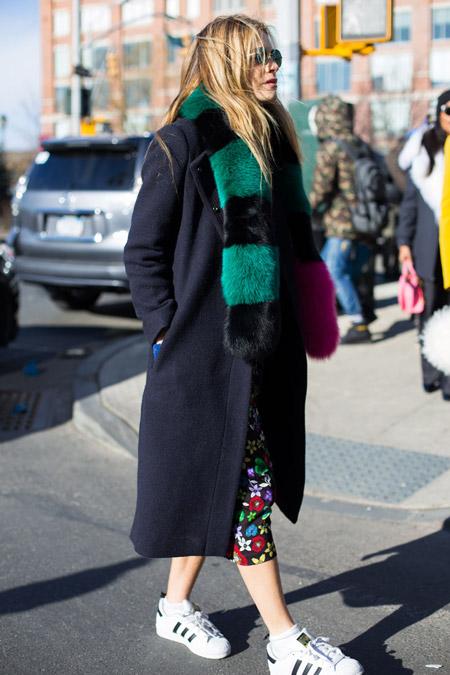 Девушка в кроссовках, сминем пальто прямого покроя и черно зеленый меховой воротник